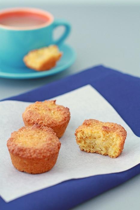 mini orange cakes set on parchment on a blue napkin with a blue tea cup