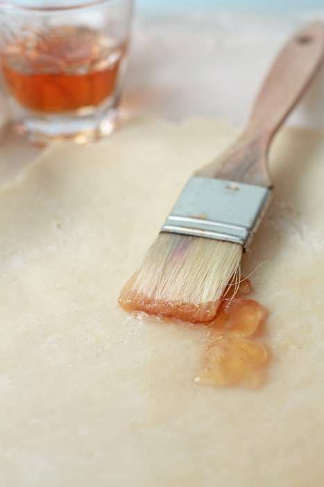 Brushing pie crust with apple jelly with a pastry brush