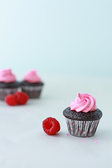 mini chocolate cupcakes with raspberry frosting and fresh raspberries