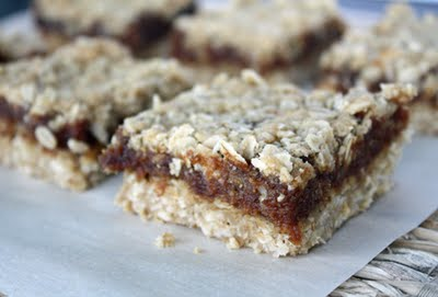 Side view of date squares to show layer of oat crumble base, date paste in the middle, and oat crumble topping