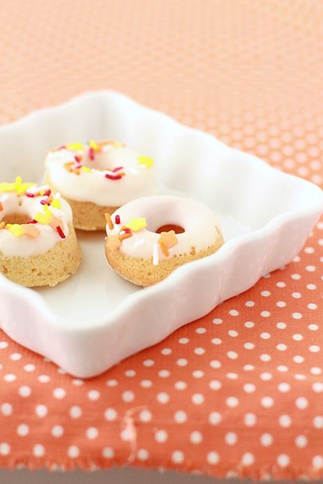 Three mini glazed pumpkin donuts on a white dish on a orange and white polka dot tablecloth