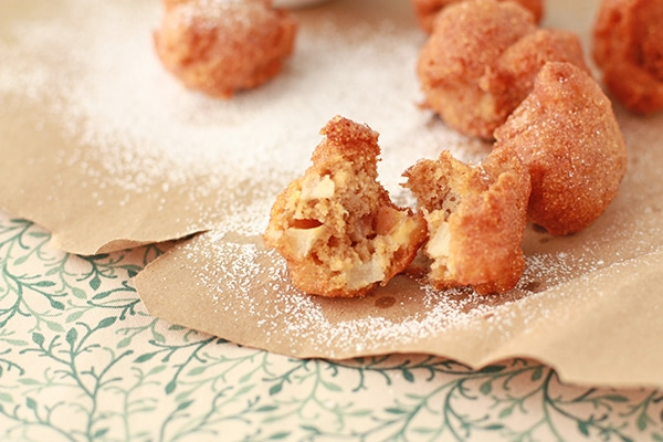 apple fritters on brown paper dusted with icing sugar