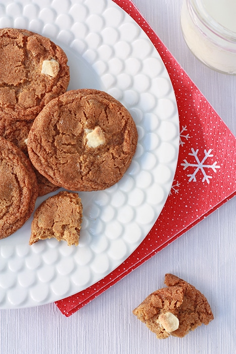 ginger cookies on a white plate with red napkin and glass of milk