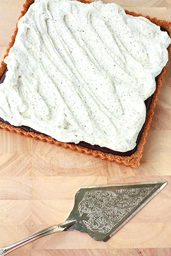 a square chocolate tart on a wood board topped with swirls of Earl grey whipped cream