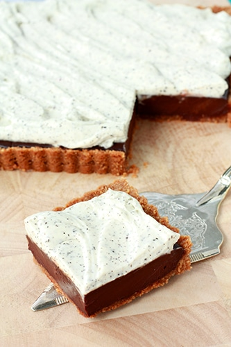 a square of chocolate tart with Earl Grey tea flecked whipped cream and a graham cracker crust placed on a silver server
