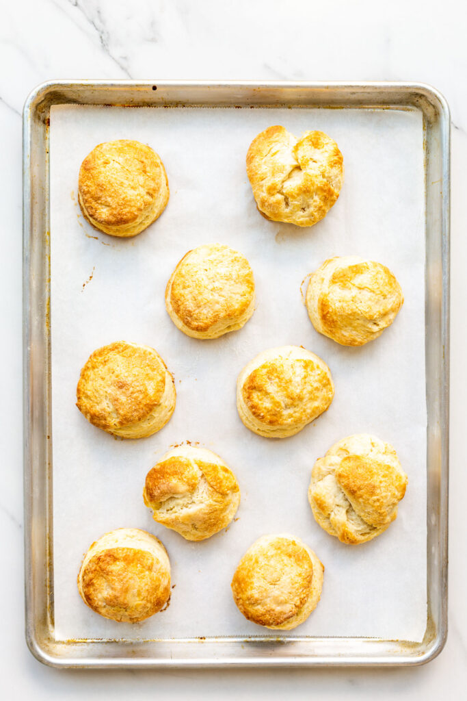 A parchment-lined sheet pan with golden brown homemade biscuits