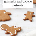 Gingerbread cookies being decorated with a piping bag of royal icing.