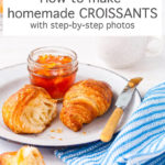 Homemade croissants served on a white enamelware plate with a blue rim and a jar of orange marmalade, blue and white striped napkin, knife with