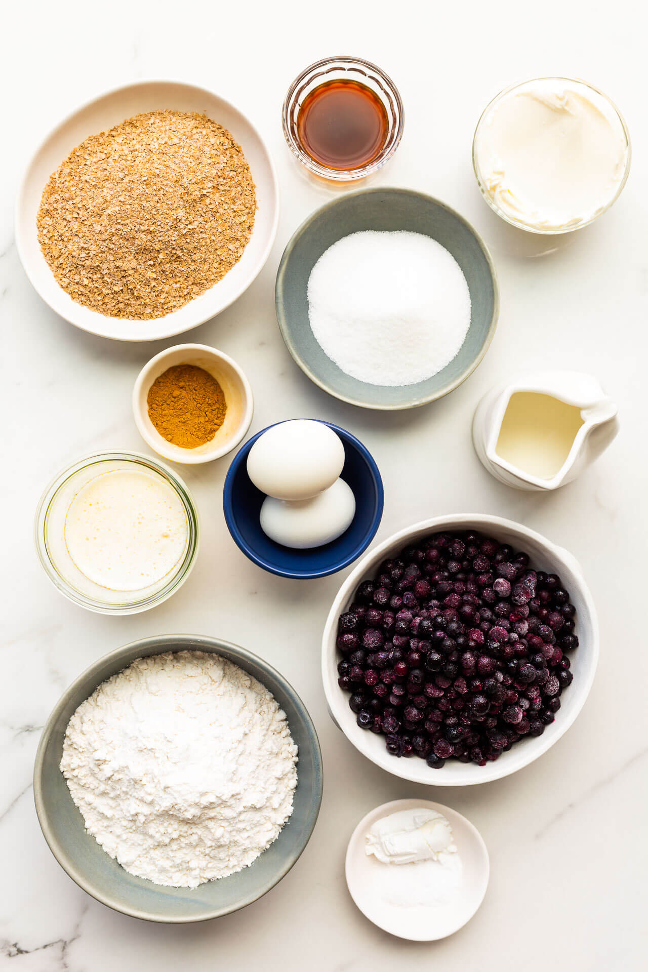 Ingredients to make blueberry bran muffins measured out into bowls, ready for mixing