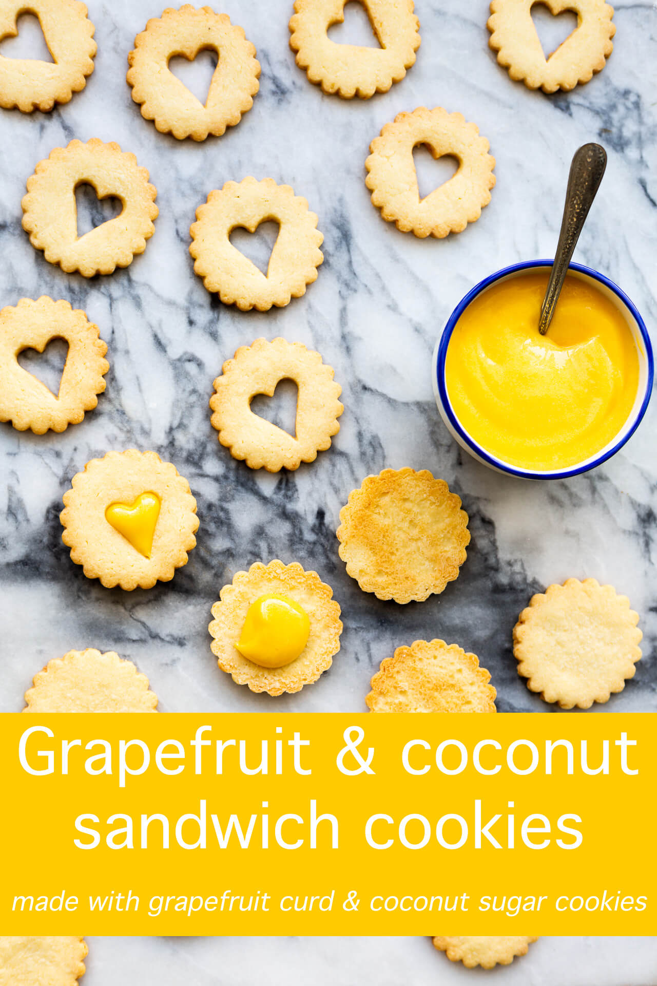 Golden buttery coconut crinkle cut round cookies with heart cut out for sandwiching with bright grapefruit curd in a bowl with a spoon