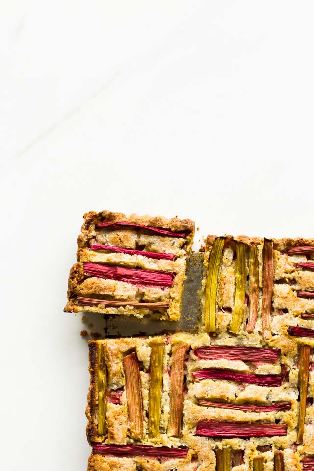 Rhubarb pumpkin seed cake sliced into squares with woven rhubarb pattern