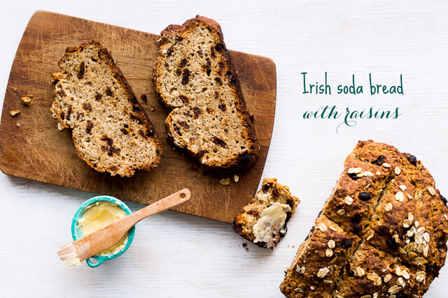Sliced loaf of Irish soda bread with raisins served with softened butter on a dark wood cutting board