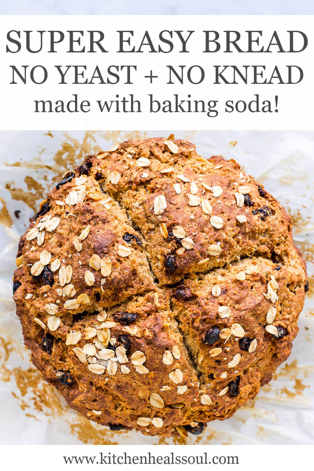 Irish soda bread with raisins topped with oats and scored with a big X on top, on parchment paper