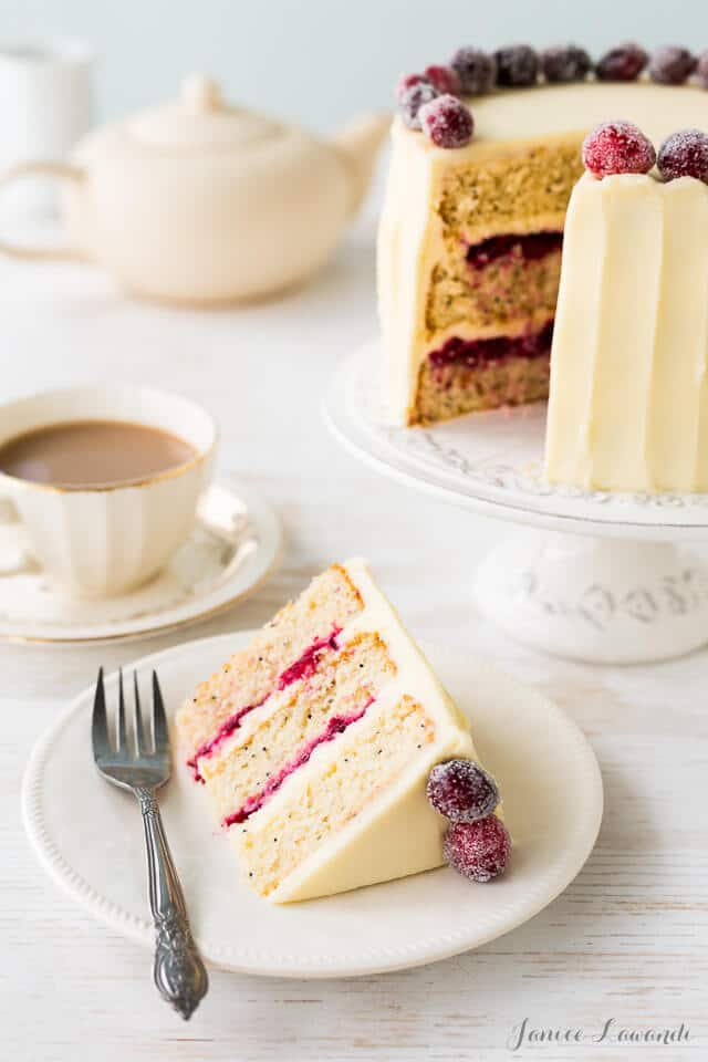 Cranberry cardamom cake sliced with cream cheese frosting and sugared cranberries