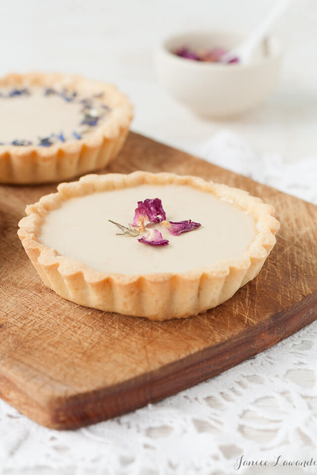 Little Earl Grey panna cotta tarts topped with dried rose petals and dried cornflower petals, served on a wooden cutting board placed on a white lace doily