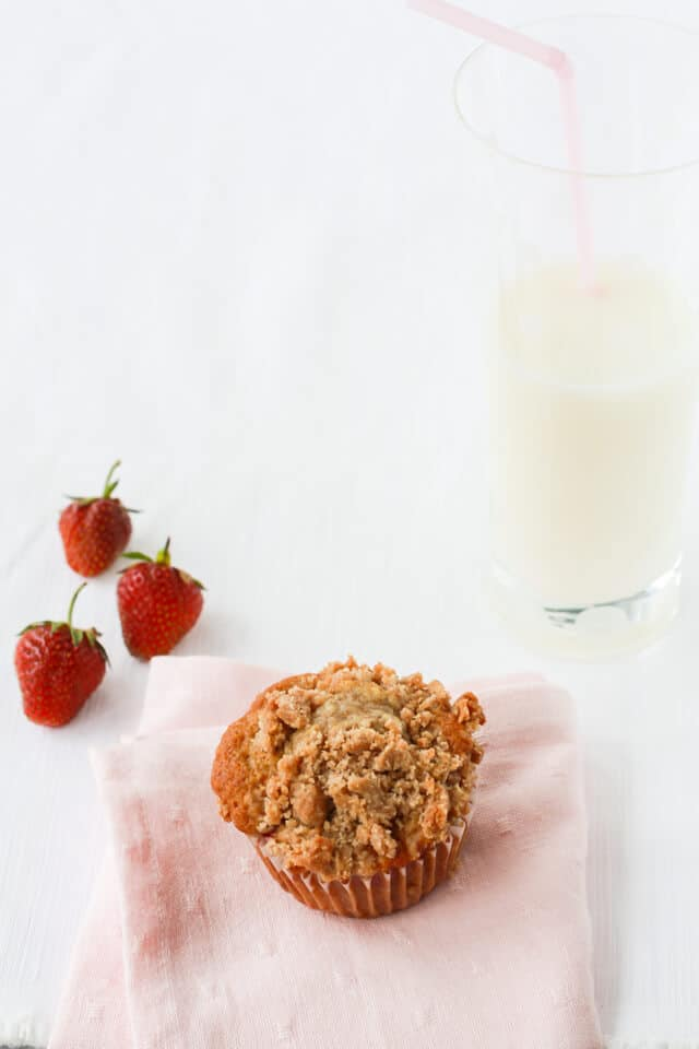 Strawberry rhubarb muffins with crumb topping and a glass of milk, pink napkin, 3 strawberries on the side
