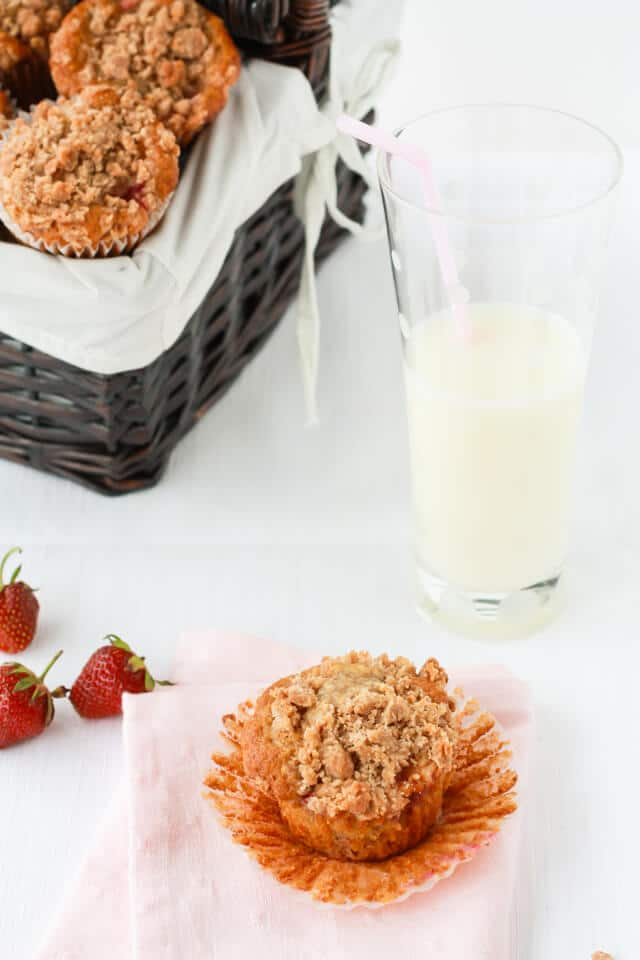 Strawberry rhubarb muffins with streusel crumbled on top served in a basket with a glass of milk