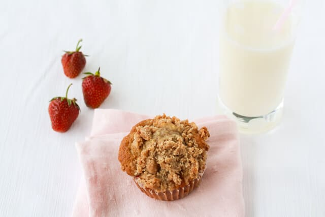 Strawberry rhubarb muffins topped with a crumble topping served with a glass of milk and fresh strawberries