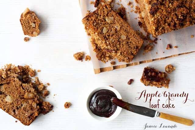 Sliced apple brandy loaf cake with streusel on a cutting board with a little dish and a knife of apple butter to serve on the sliced bread