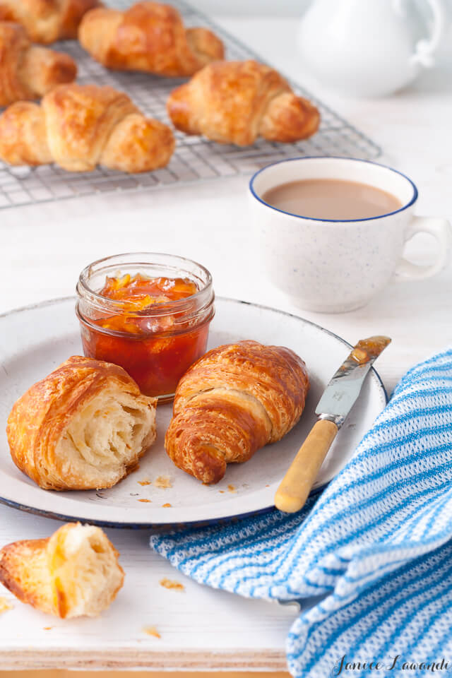 Croissant breakfast consisting of homemade croissants with a jar of orange marmalade served on a white enamelware plate with a blue rim, a knife, a blue and white striped napkin and a cup of coffee. Cooling rack of homemade croissants in the background