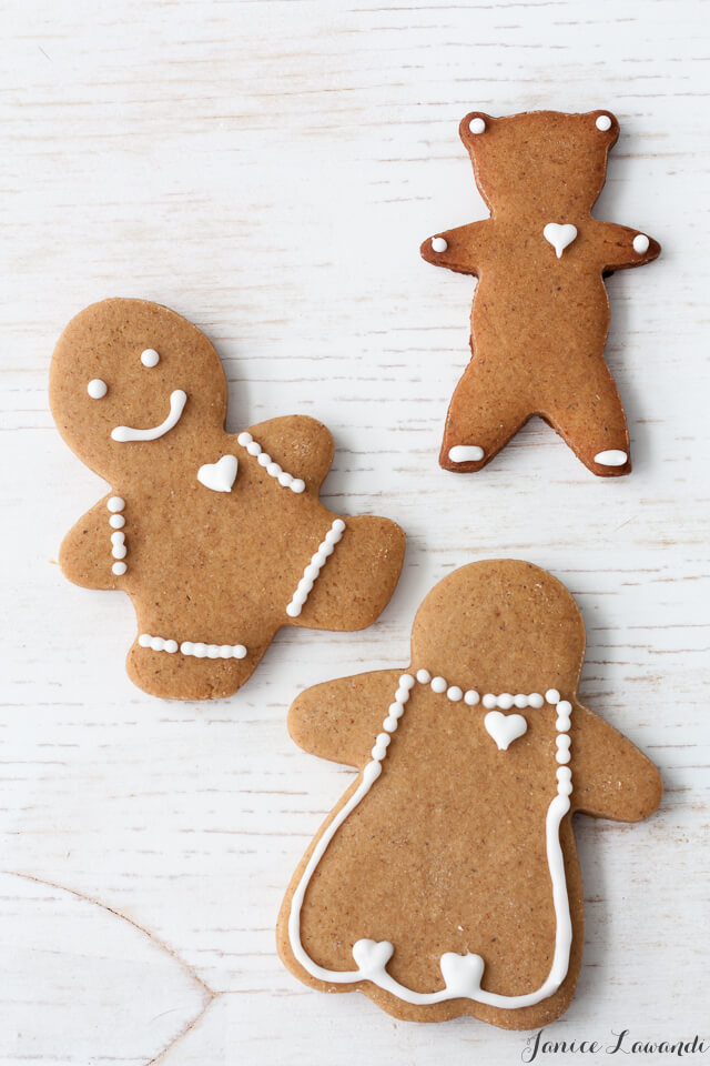Decorated gingerbread cookie cutouts of a boy, a girl, and a teddy bear.