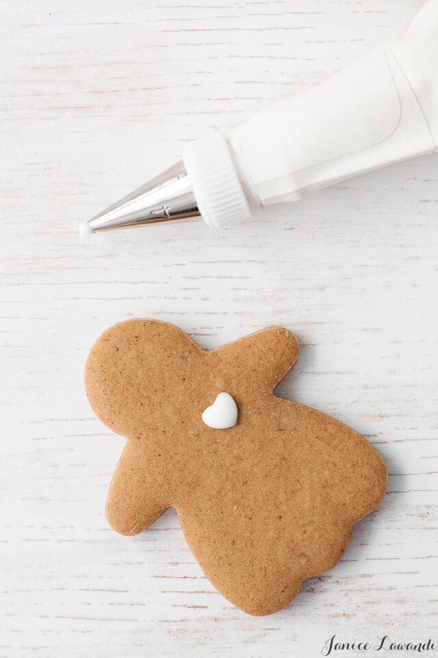 A gingerbread girl being decorated with royal icing with a heart piped on her chest.