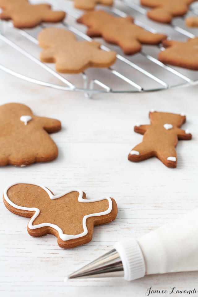 Decorating gingerbread cookie cutouts with a piping bag of royal icing.