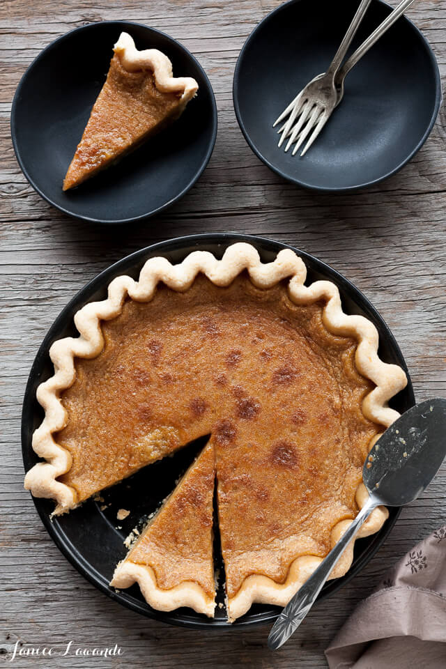 Maple syrup pie sliced and served with a pie lifter on black matte dishes