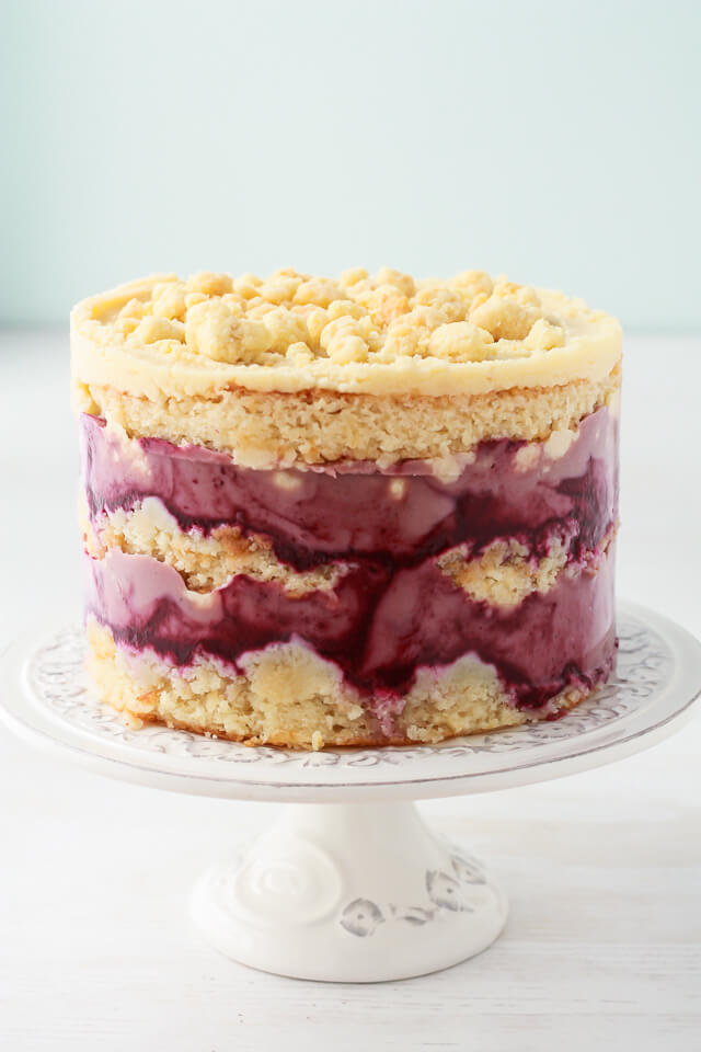 Milk crumbs on a Momofuku Milk Bar style cake-layers of purple blackberry curd, cream coloured almond cake, and creamy almond frosting