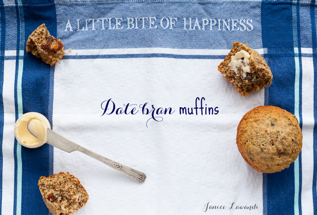 "Date bran muffins served with butter and butter knife on a tea towel with blue plaid print and ""A little bite of happiness"" text printed on towel"