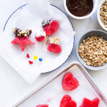 Frozen watermelon pops dipped into melted chocolate and granola or other fun toppings