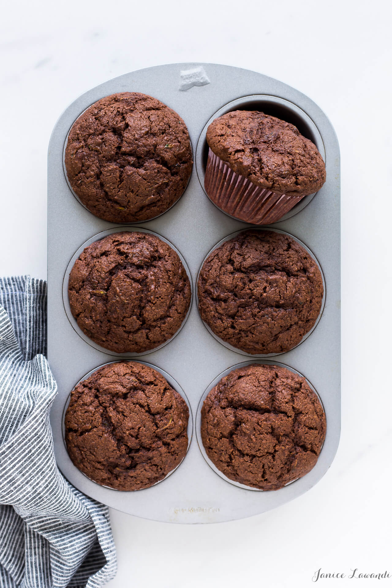 Zucchini chocolate muffins baked in a muffin pan with paper liners