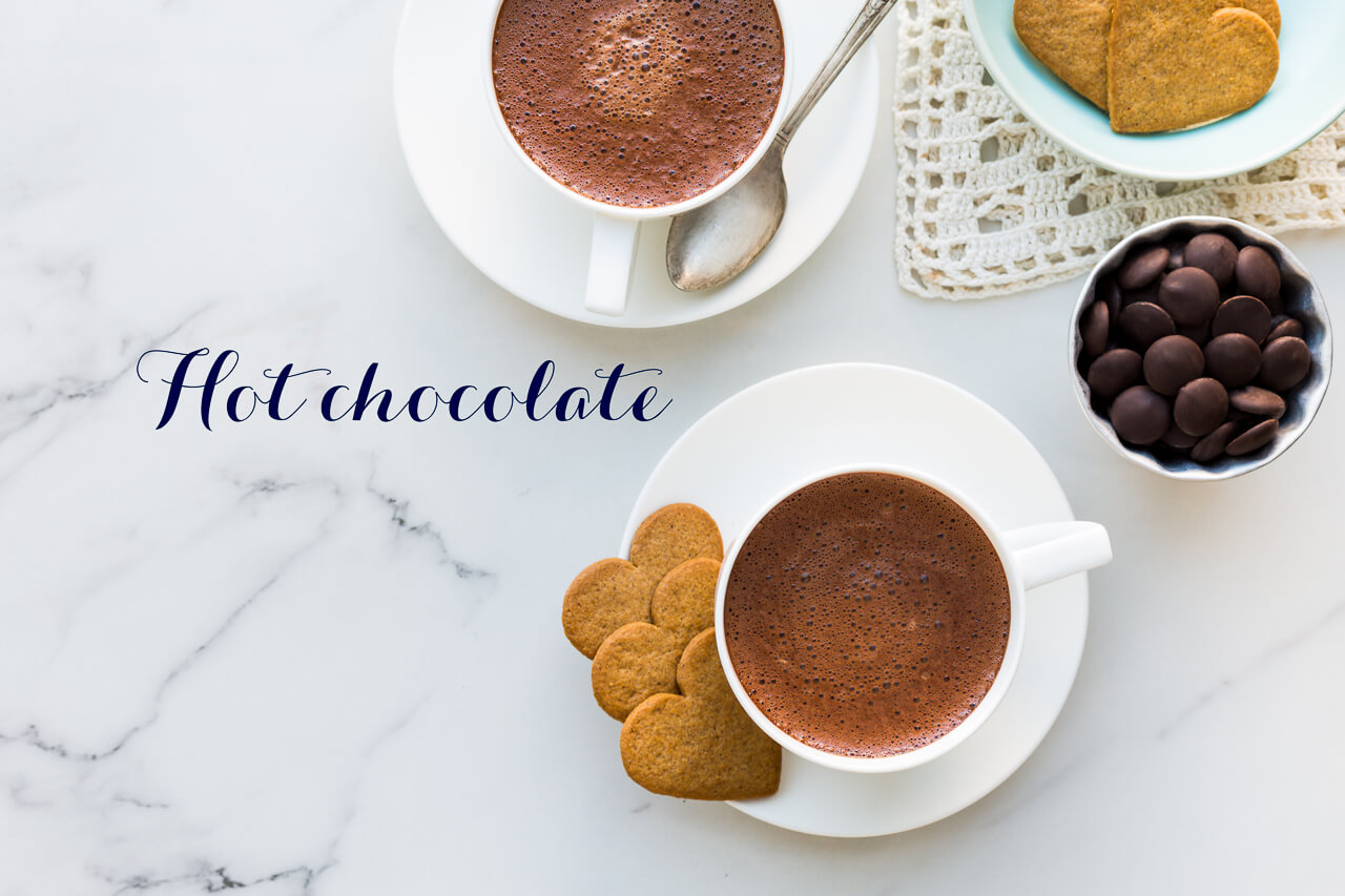 Two white cups of homemade hot chocolate made with 70% dark chocolate served with heart-shaped gingersnaps
