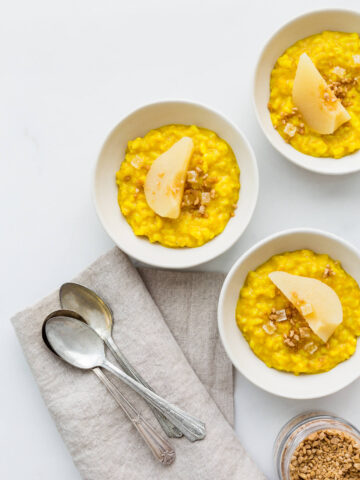 Golden milk rice pudding spiced with turmeric, ginger, cardamom, and cinnamon served with poached pears