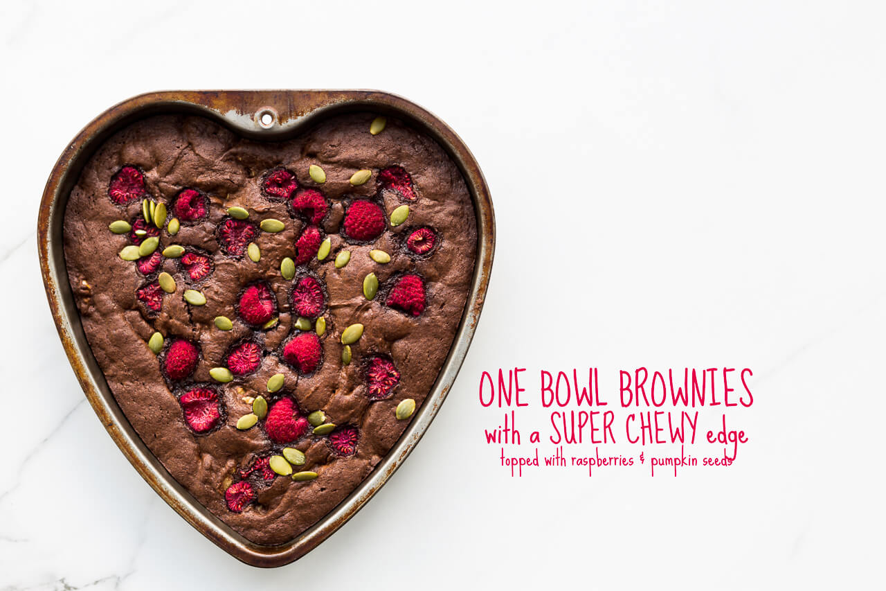A recipe for one bowl brownies with walnuts and a super chewy edge, baked in a heart shape pan and topped with raspberries and pumpkin seeds