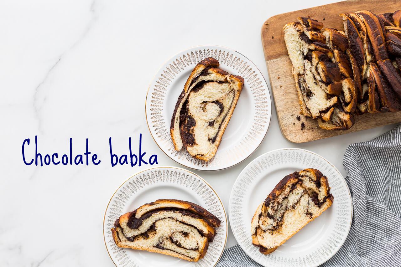 Chocolate swirl babka loaf sliced on a wooden cutting board