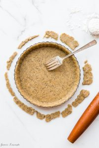 Coffee sablé cookie crust - the raw crust is being docked (pricked) with a fork to allow steam/air to vent during baking. The crust will be blind baked
