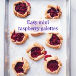 mini raspberry galette pies cooling on a parchment-lined baking sheet