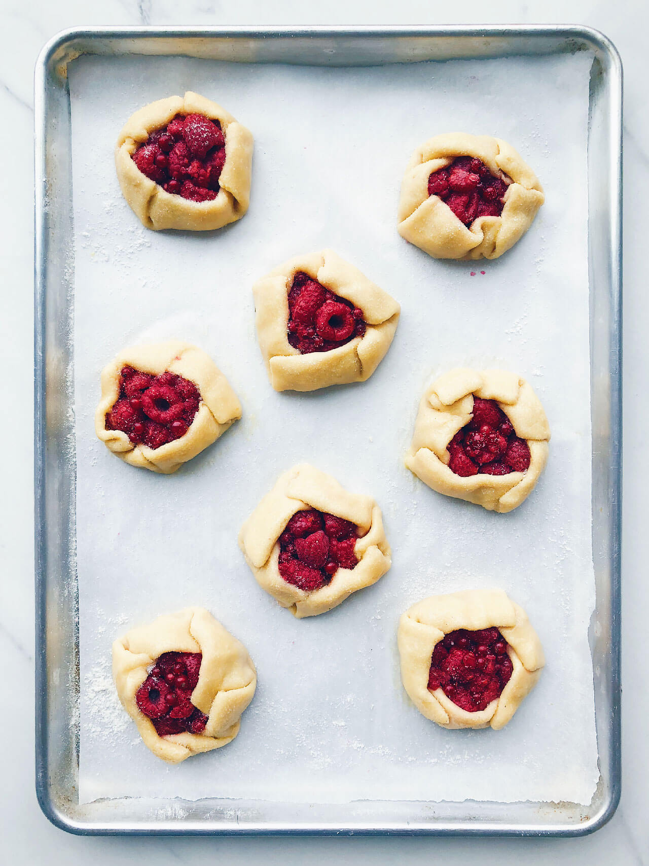 Homemade freeform mini raspberry galettes shaped and ready for the oven on a parchment-lined baking sheet