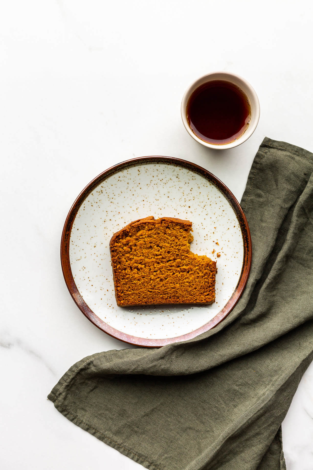 A slice of pumpkin spice bread with a bite taken out of it, with a green linen and a cup of tea on the side.