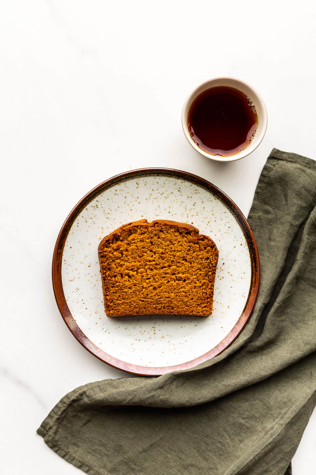 A slice of pumpkin spice loaf cake with a cup of tea and a green linen.