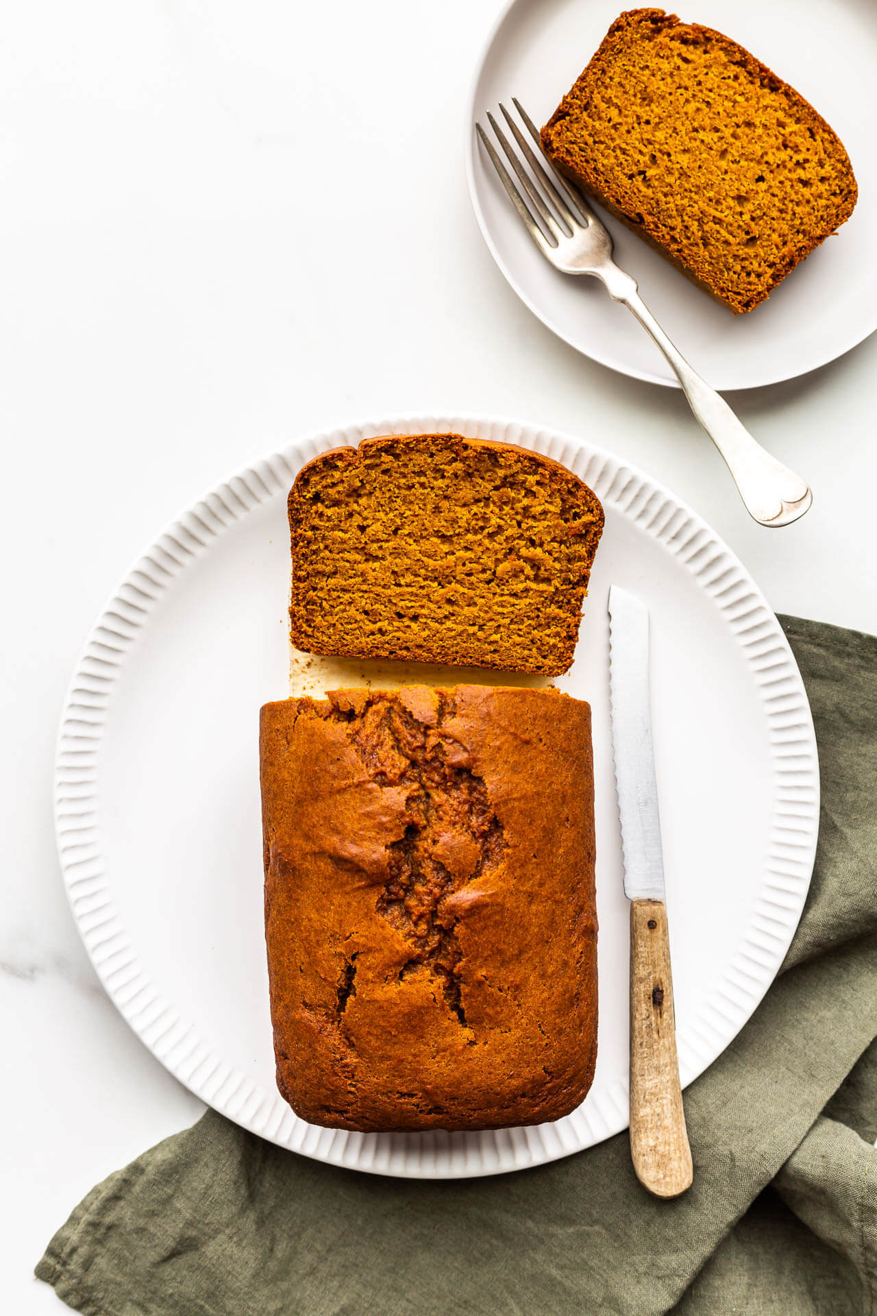 Slicing and serving a loaf of pumpkin bread.