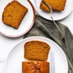 Slicing pumpkin loaf cake to serve on ceramic plates with green linen.