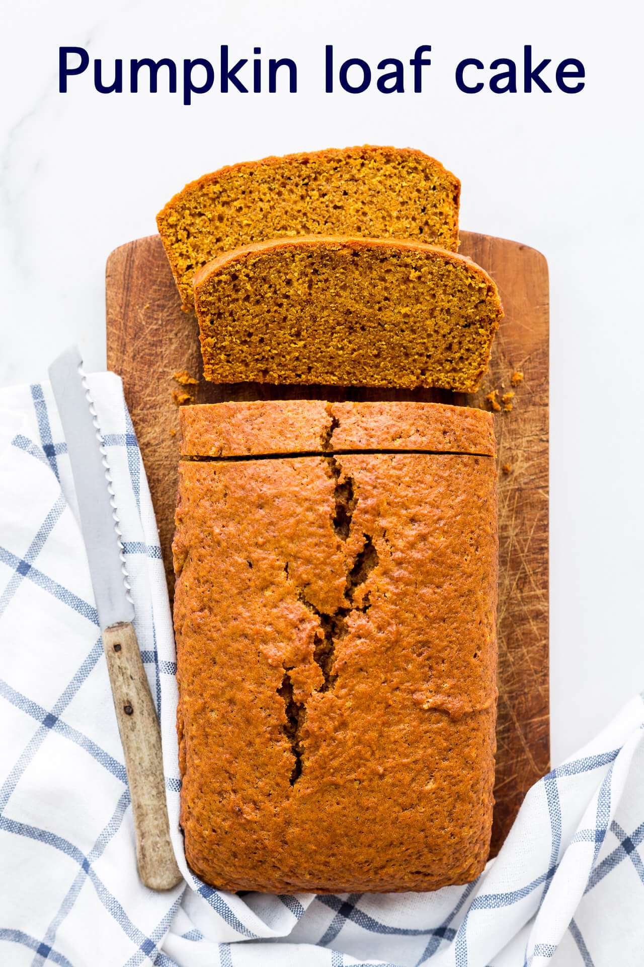 Spiced pumpkin loaf cake on a wood cutting board with a blue and white kitchen towel, sliced with a serrated knife