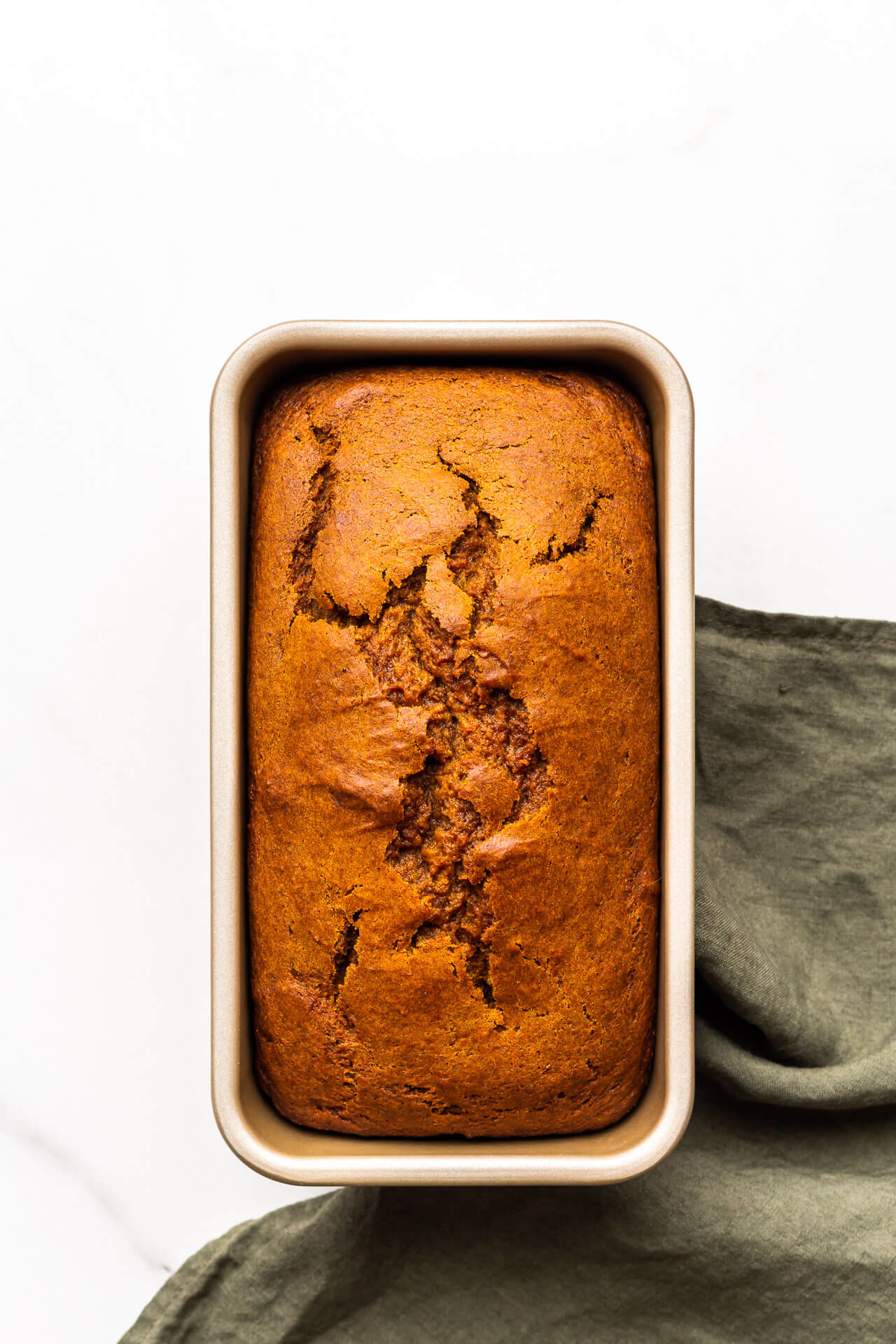 Pumpkin bread in loaf cake pan after baking with green linen.