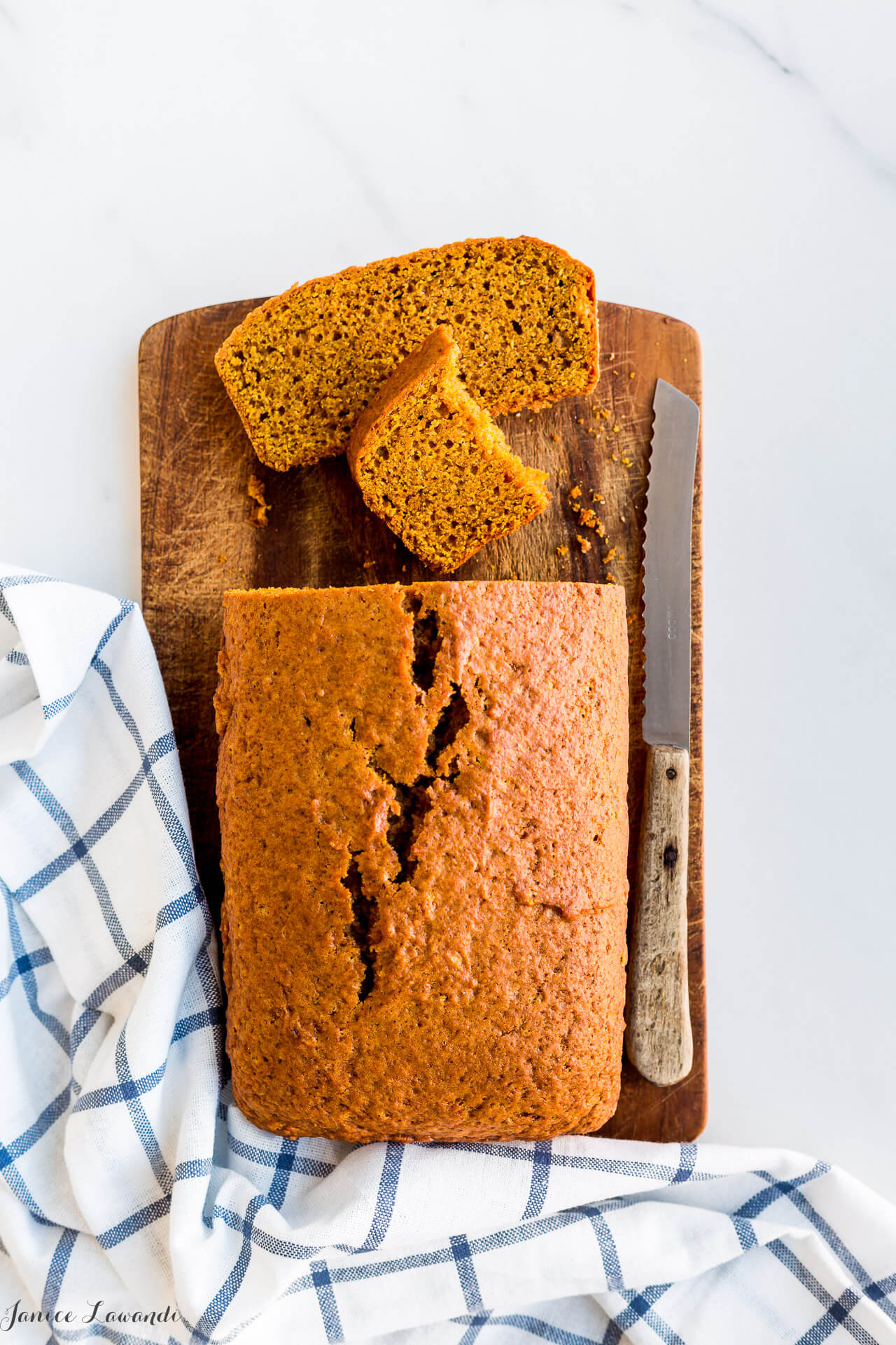 Slices of pumpkin loaf cake on a wooden cutting board with a serrated knife and a blue and white kitchen towel