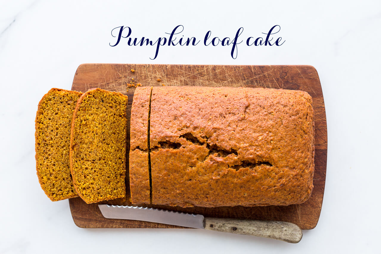 Sliced pumpkin loaf cake with a serrated knife on a wood cutting board