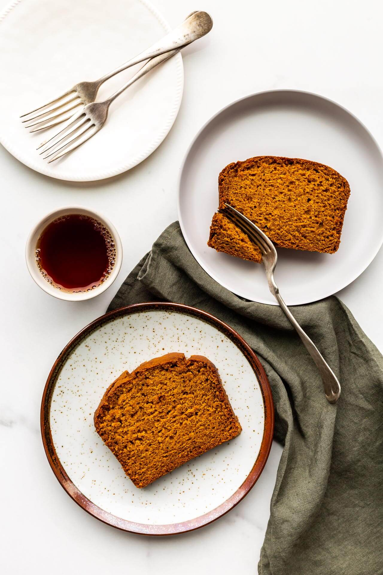 Slices of pumpkin bread served on speckled plates with a cup of tea and green linen