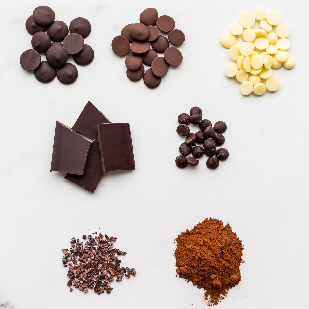 different types of chocolate, dark, milk, and white chocolate, as well as chocolate chips, cocoa nibs, and cocoa powder.