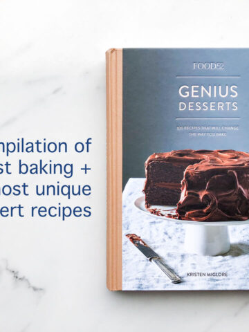 The cover of the Food52 Genius Desserts cookbook features a two layer chocolate cake with chocolate frosting on a cake stand